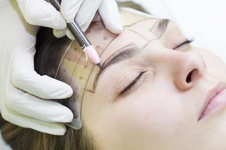 A microblading technician outlines the eyebrows of a female client.